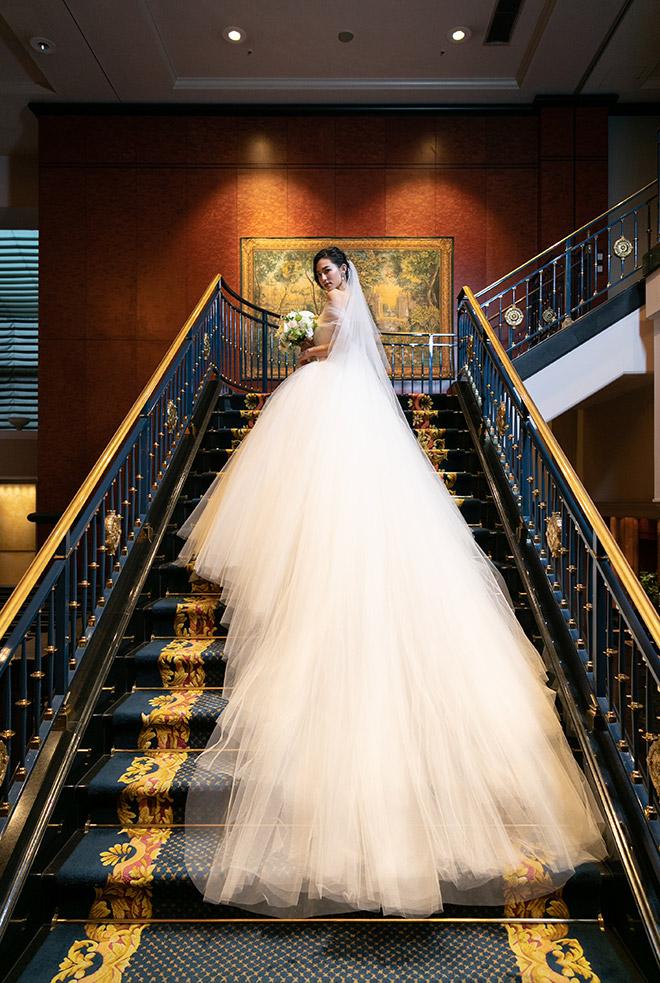 らせん階段に敷かれた気品あふれるロイヤルブルーの絨毯はウエディングドレスとのコントラストが素敵